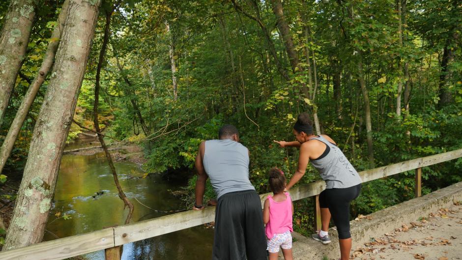 Family of three enjoying views of the river at Aman Park Trail