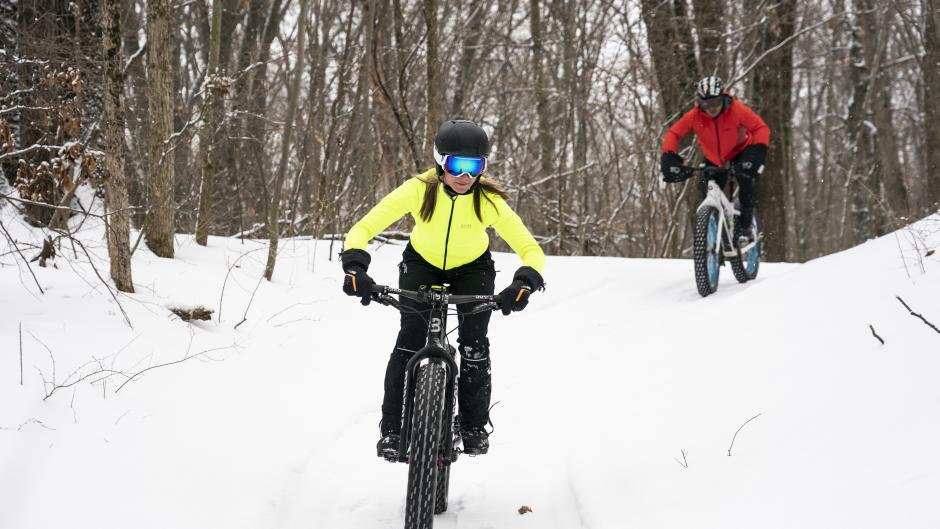 Two people biking through snowy trails