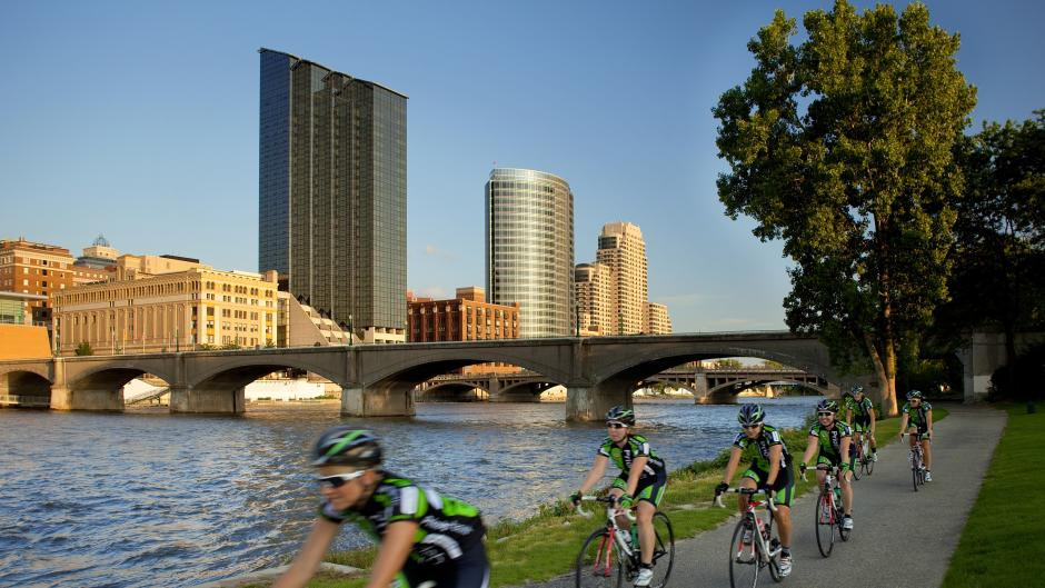 Bikers cycling through Downtown Grand Rapids along the river