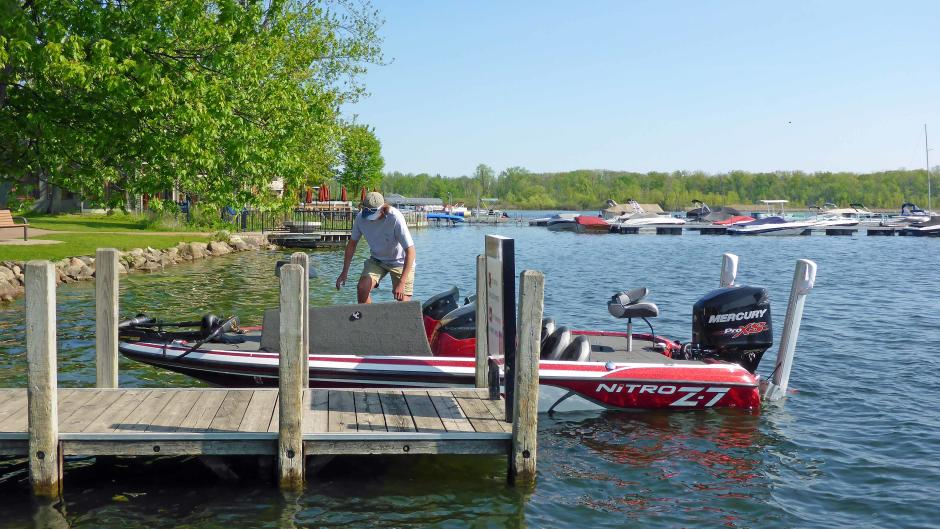 An angler readies his boat and gear after launching at John Collins Park at Reeds Lake.