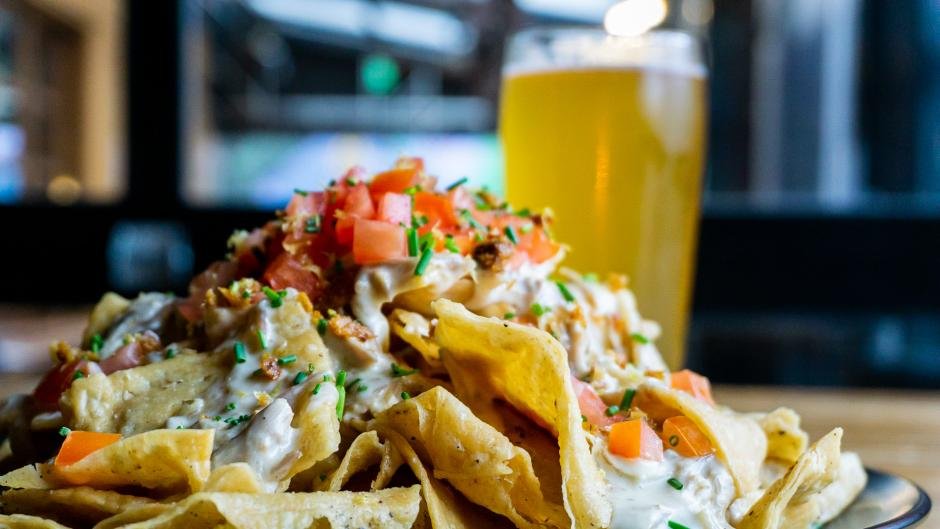 A plate piled with duck nachos with a beer in the background at Brewery Vivant.