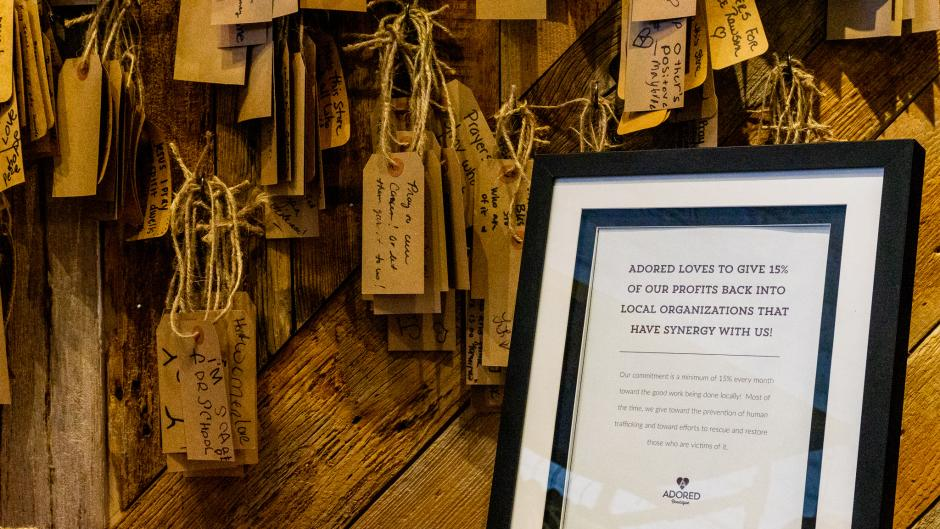 Framed sign at Adored Boutique highlighting its commitment to donate 15% of profits to local causes.