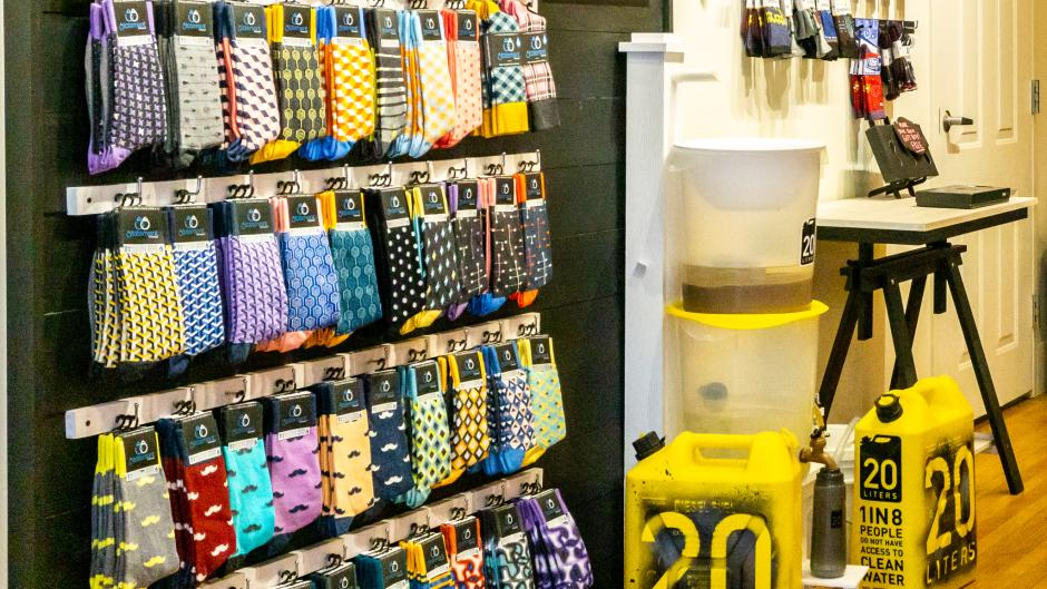 "Socks available at boldSOCKS next to water containers that say ""20 Liters."""