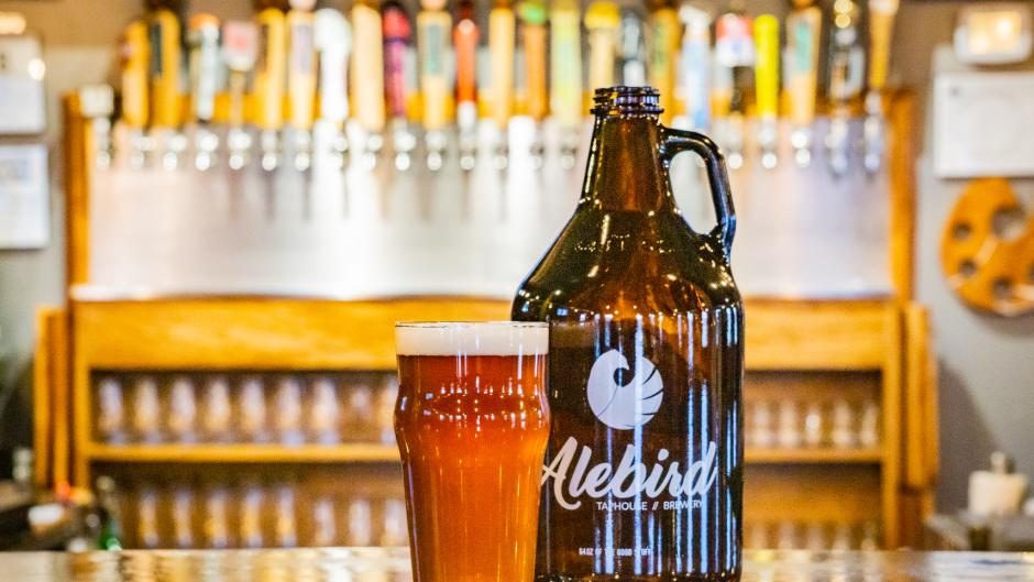 A glass of beer next to a growler container with the Alebird logo on it.