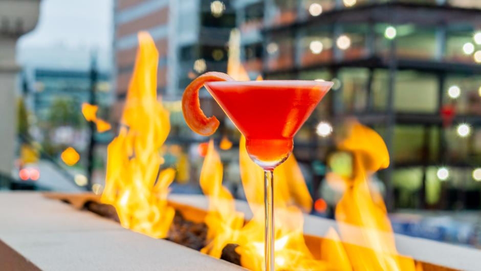 A red cocktail at IDC's patio, positioned in front of an outdoor fire pit.