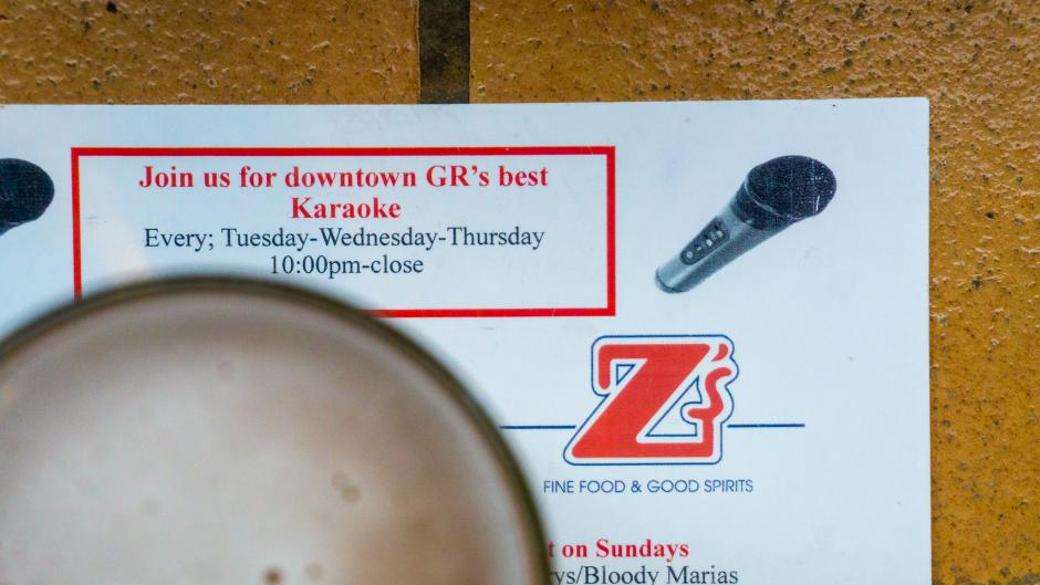"""A beer glass sitting on a menu at Z's which says """"Join us for downtown GR's best Karaoke."""""""