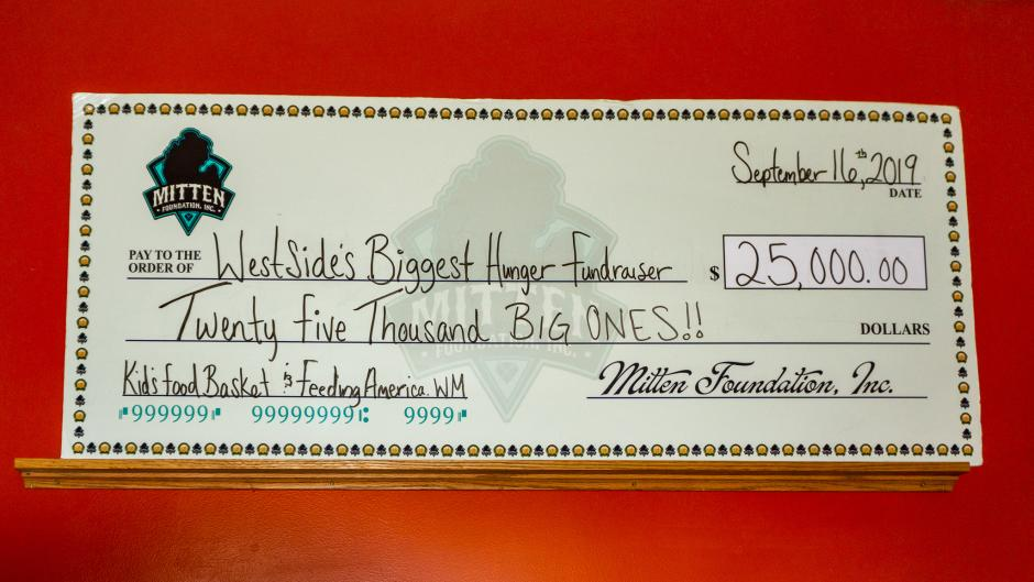 A giant check at The Mitten with the amount and charity of their monthly donation.