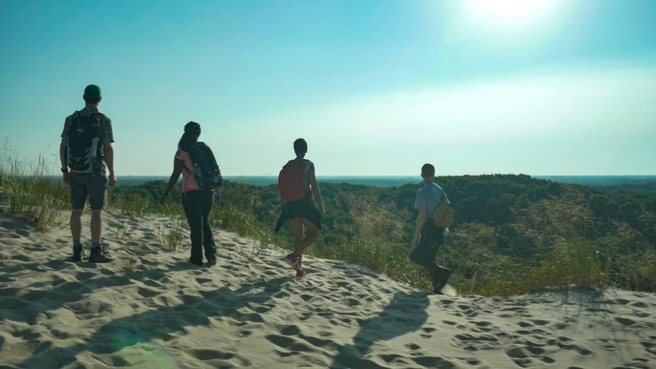 Four people hiking in sand at PJ Hoffmaster State Park near Grand Rapids