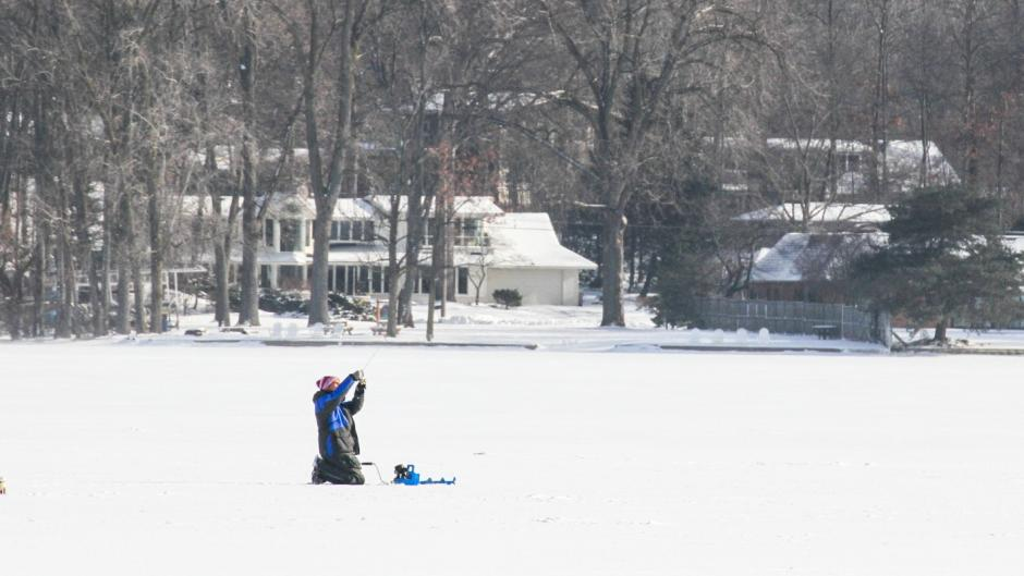 Person ice fishing on Reed's Lake.