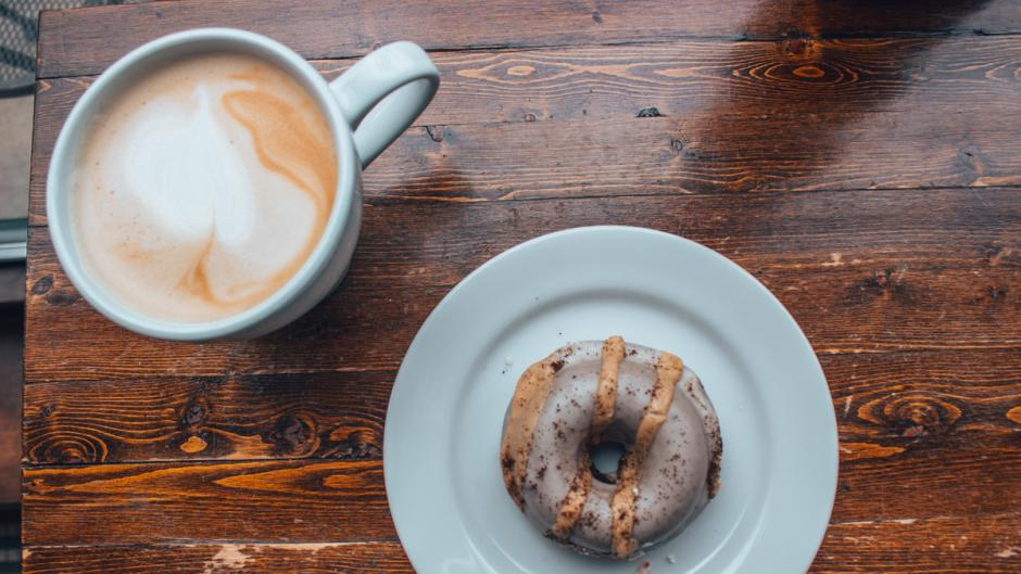 A donut on a plate next to a hot latte at the Lantern.