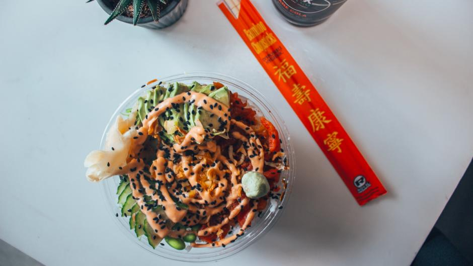 Bird's-eye view of a table holding a poke bowl, chopsticks, a soda, and a succulent.