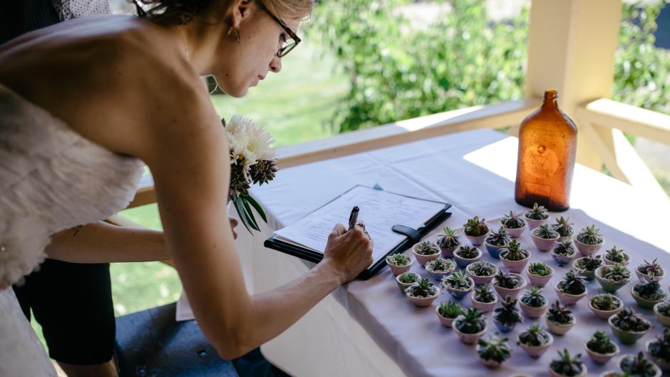 Bride signing next to succulent party favors.