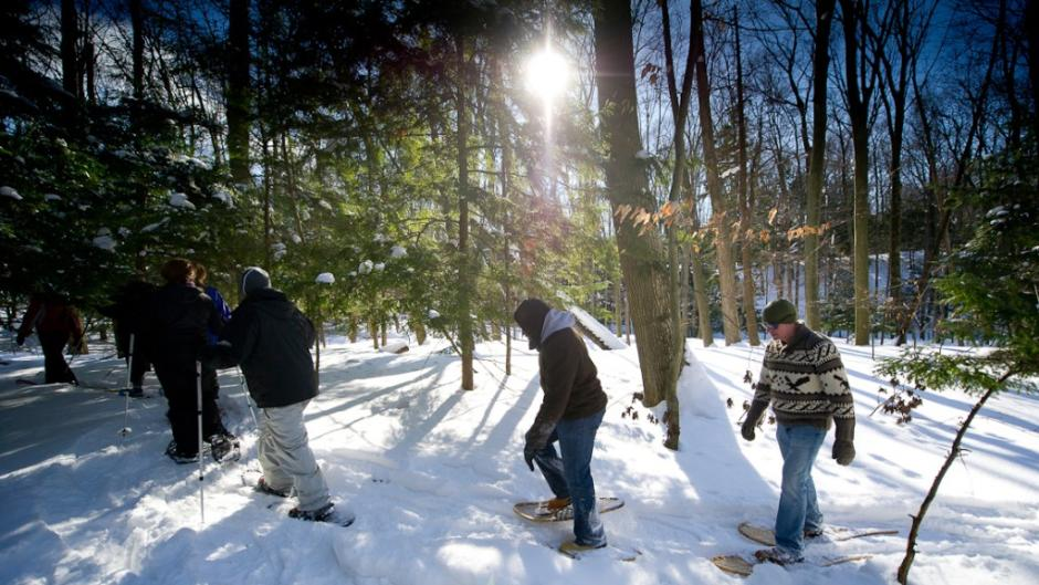 A group enjoys a guided snowshoe hike at P.J. Hoffmaster State Park where wooden snowshoes can be rented.