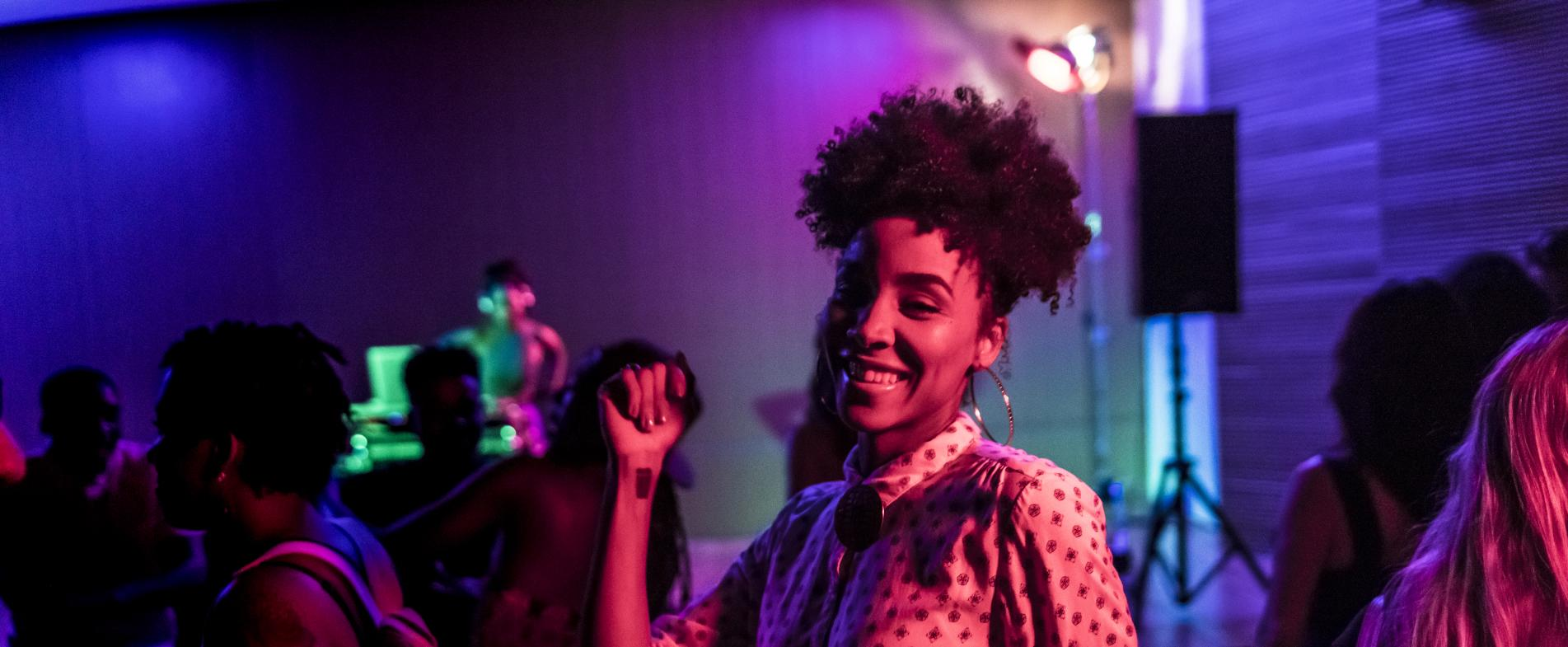 Smiling woman dancing at a night club in Grand Rapids