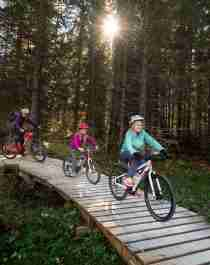 A family of four is biking through the woods in Trysil bike arena in Trysil, Eastern Norway