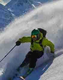 En person står på ski ned en fjellside på Helgeland i Nord-Norge