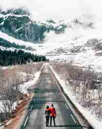 To personer går på en vei i et vinterkledd Lofoten i Nord-Norge