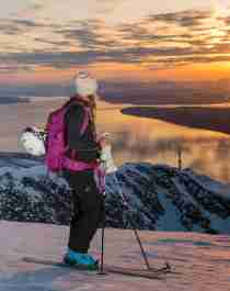Two women with skis enjoying the view of mountains and fjord from the top of a mountain in Narvik, Northern Norway
