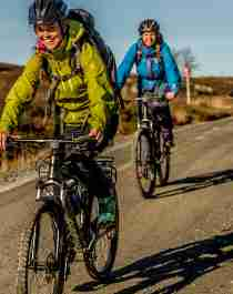 Three people cycling at a dirt road on the Hardangervidda mountain plateau in Eastern Norway