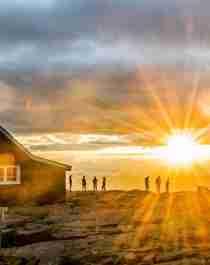 Folk ser på solnedgangen utenfor Fannaråkhytta i Jotunheimen