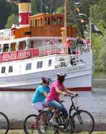 Cyklister passerar en kanalbåt på den nationella cykelvägen längs Telemarkskanalen i regionen Østlandet (östra Norge)