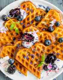 A plate of waffles with sour cream and berries
