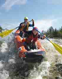 Two people rafting down the Trysil river in Eastern Norway