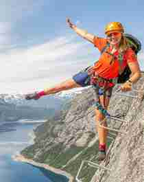 Active holiday in Norway: Woman climbing the Trolltunga via ferrata in Fjord Norway