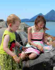 Two kids sitting on rocks next to the sea and try geocaching in Sandnessjøen in Nordland, Northern Norway