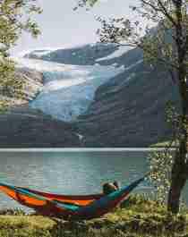 People in hammocks in front of the Svartisen glacier in Helgeland, Northern Norway