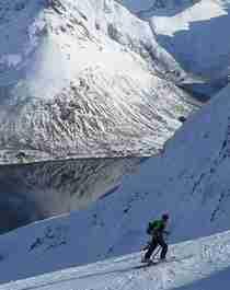 A ski tourer on his way up Mount Kvittinden in Lofoten, Norway