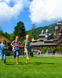 Children running in front of the Fairy tale castle in Hunderfossen family park in the Lillehammer region, Eastern Norway