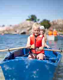 Two children in a rowing boat near Bragdøya outside of Kristiansand, Southern Norway