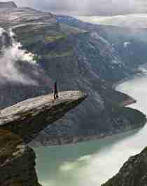 A person standing on Trolltunga facing the Ringedalsvatnet lake in Hardanger, Fjord Norway