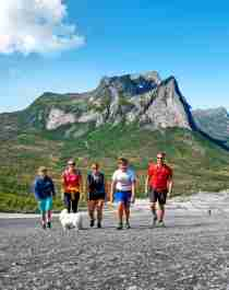 A family is hiking the Verdenssvaet hill by Efjorden in Narvik, Northern Norway