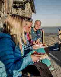 Tre mennesker spiser vafler utenfor Gaustatoppen turisthytte i Telemark
