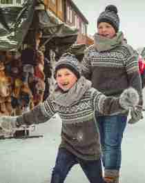 Two smiling children next to the stalls at Røros Christmas Market in Trøndelag, Norway