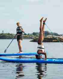 Two people are stand up paddleboarding in Southern Norway