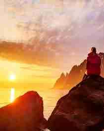 En person ser på midnattssola på Senja i Nord-Norge