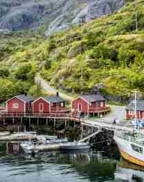 Boats and red fisherman's cabins along the small harbour of Nusfjord in Lofoten, Northern Norway