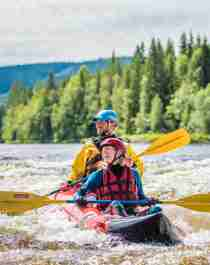 Two people packrafting down the river in Trysil, Eastern Norway