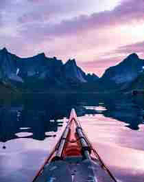 The tip of a kayak and steep mountains in the midnight sun in Lofoten, Northern Norway