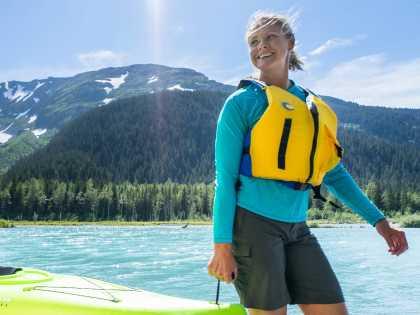 A couple carries a kayak along the shore of Explorer Lake.