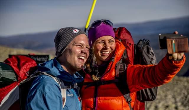 Een koppel dat een selfie neemt bovenop de berg Gaustatoppen in Telemark, Noorwegen