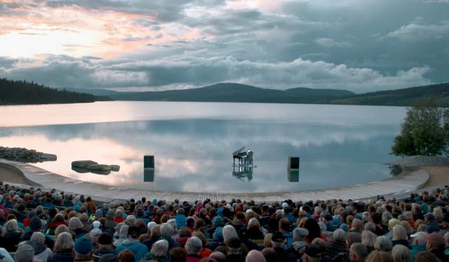 A pianist playing the grand piano on the Gålåvatnet lake, in front of an audience. The Peer Gynt Festival, Norway