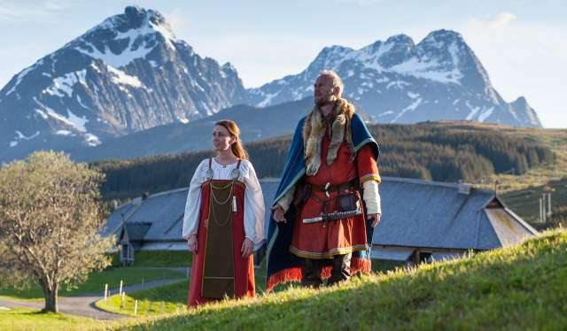 To vikinger står foran høvdingshuset på Lofotr Vikingmuseum i Lofoten