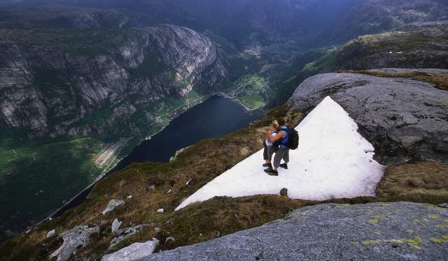 Couple on Mount Kjerag in Fjord Norway admiring view of the Lysefjord