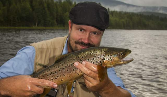 Teacher in fly fishing, Tore Litlere Rydgren in a river holding a fish