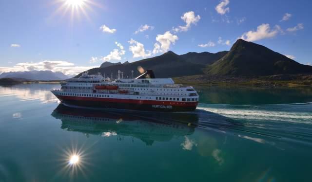 Een Hurtigruten-schip in Noorwegen met de zon die in het water reflecteert