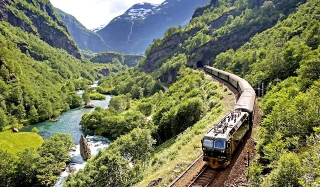Et tog kjører på Flåmsbana gjennom en grønn og frodig dal